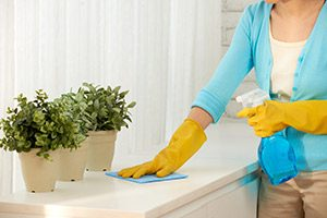 A woman wiping down surfaces to prevent dust bunnies